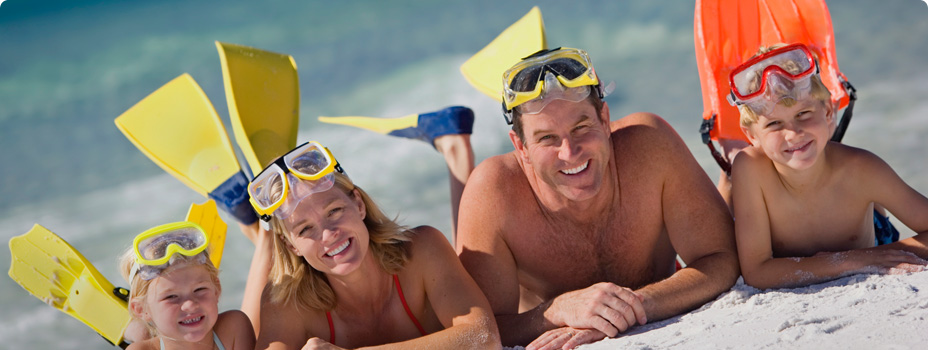 Happy Family with snorkel gear on the beach